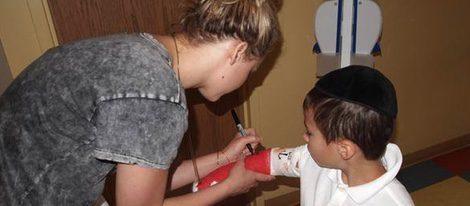 Jennifer Lawrence firmando la escayola de uno de los pequeños