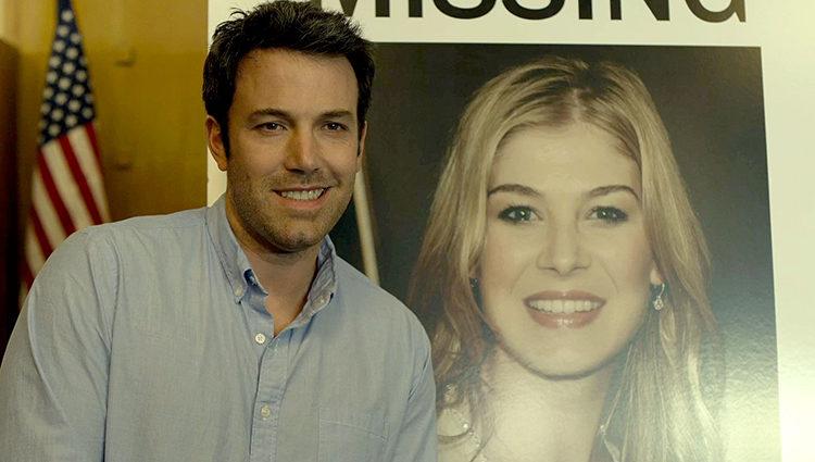 Ben Affleck, como Nick Dunne, posa junto a la foto de su esposa en 'Perdida'