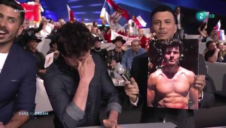 Momento en el que el presentador muestra la fotografía de Miki sin camiseta