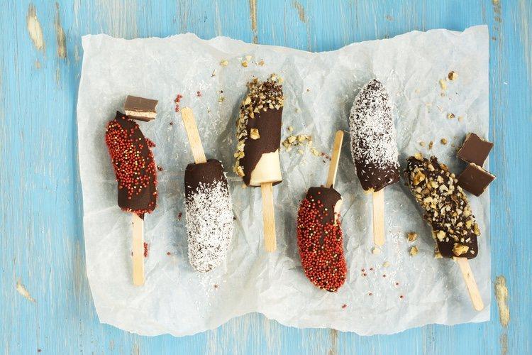 El platano con chocolale helado es una manera original y divertida de comer fruta