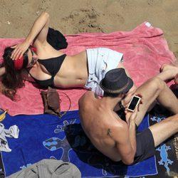 Sergio Mur consulta su móvil junto a Olivia Molina