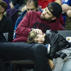 Milan Piqué apoya la cabeza junto a su padre Gerard Piqué en un partido de baloncesto