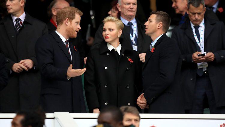 El Príncipe Harry charlando con Charlene de Mónaco y Gareth Wittstock en un partido de rugby