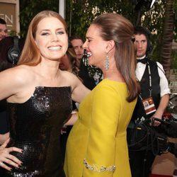 Amy Adams y Natalie Portman saludándose en la alfombra roja de los Globos de Oro 2017