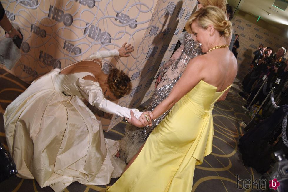Reese Witherspoon ayudando a levantarse a Sarah Jessica Parker en la fiesta de HBO tras los Globos de Oro 2017