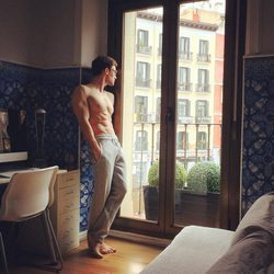 Escaleto con el torso desnudo mirando por la ventana