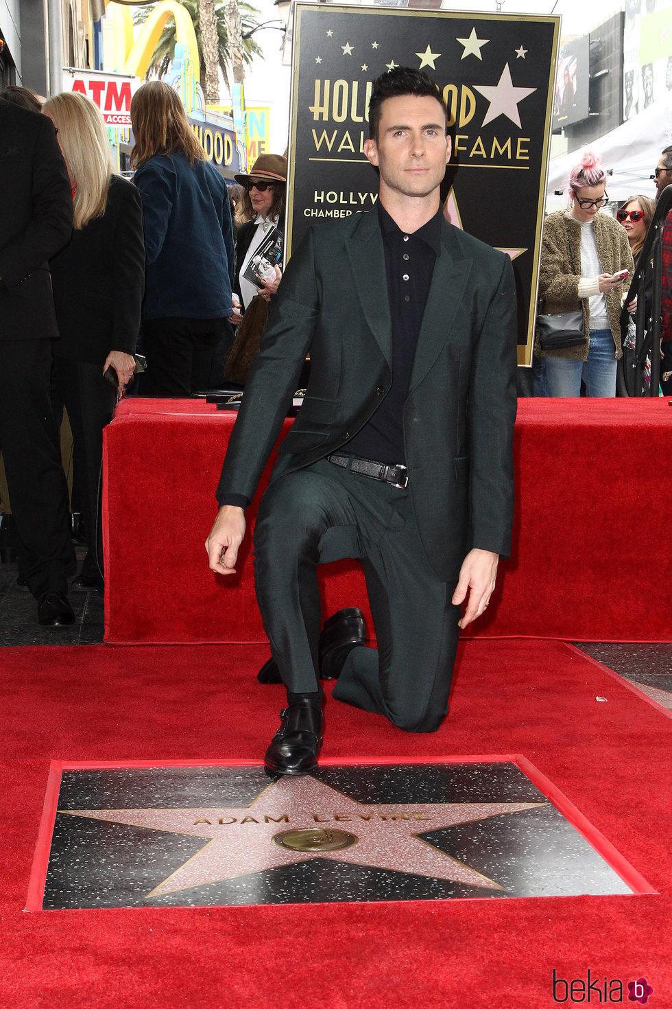 Adam Levine posando con su estrella en el Paseo de la Fama