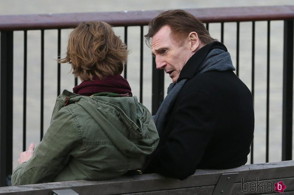 Liam Neeson y Thomas Brodie Sangster sentados en un banco en una de las secuencias de 'Love Actually 2'