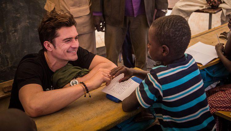 Orlando Bloom sonríe a un niño en un campamento de Unicef