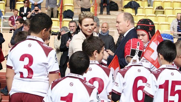 Alberto y Charlene de Mónaco con unos niños en el Torneo de Rugby de Santa Devota