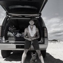 Ryan Phillippe en la playa apoyado sobre un coche