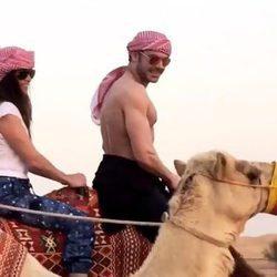 Zac Efron montando en camello con una amiga en Dubái
