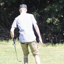 Justin Bieber jugando a golf y enseñando su tatuaje de Cristo