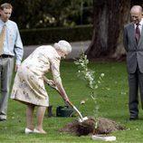 La Reina Isabel planta un árbol mientras el Duque de Edimburgo le observa