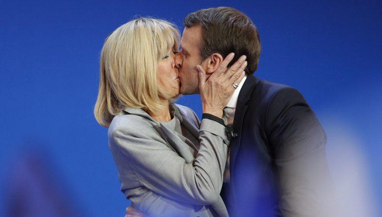 Emmanuel y Brigitte Macron besándose en una acto público