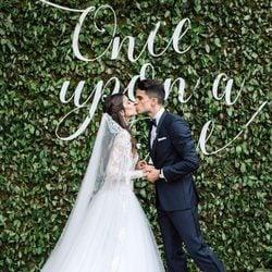 Marc Bartra y Melissa Jiménez besándose frente a un cartel de 'Once upon a time'