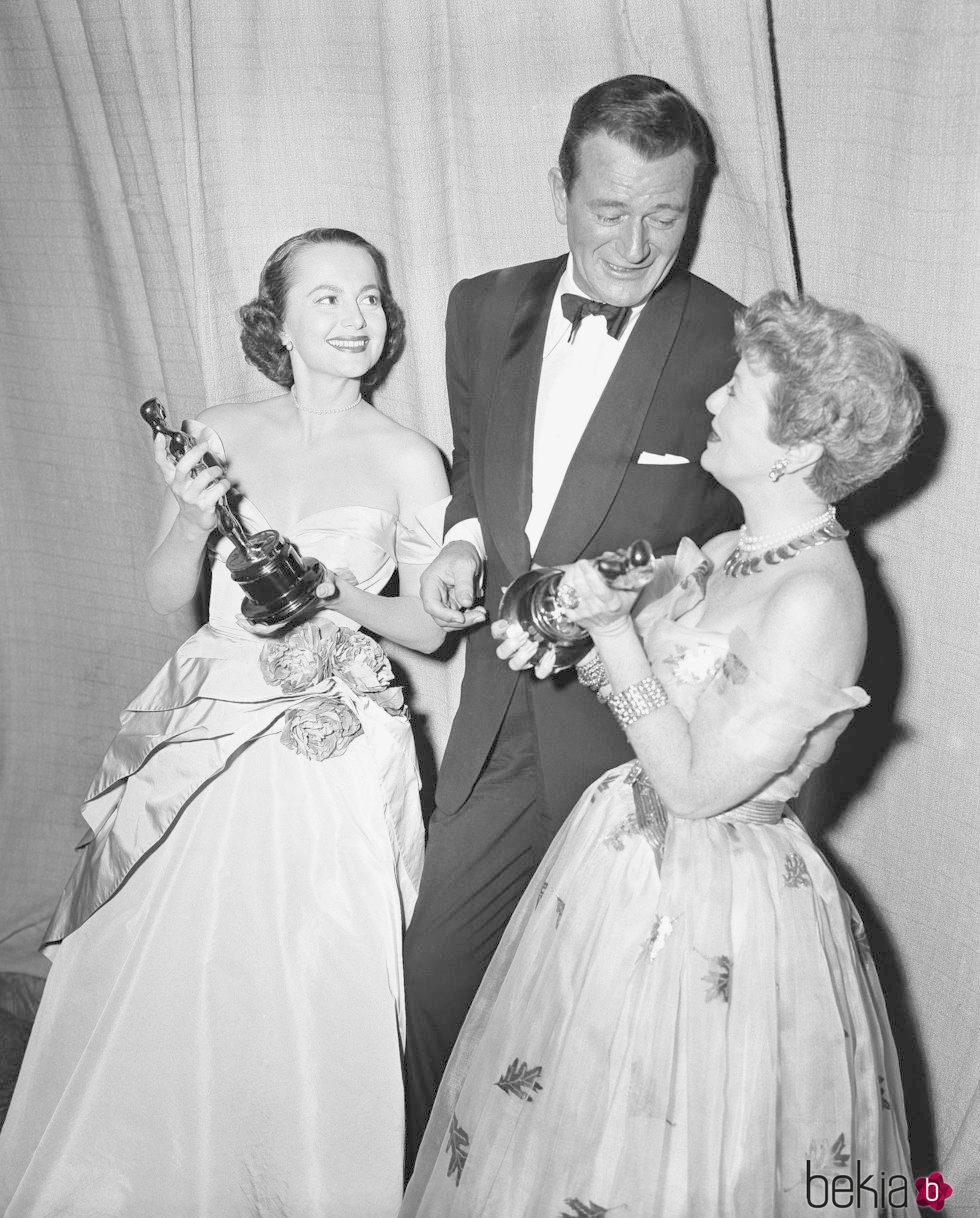 Olivia de Havilland recogiendo su Oscar junto a John Wayne