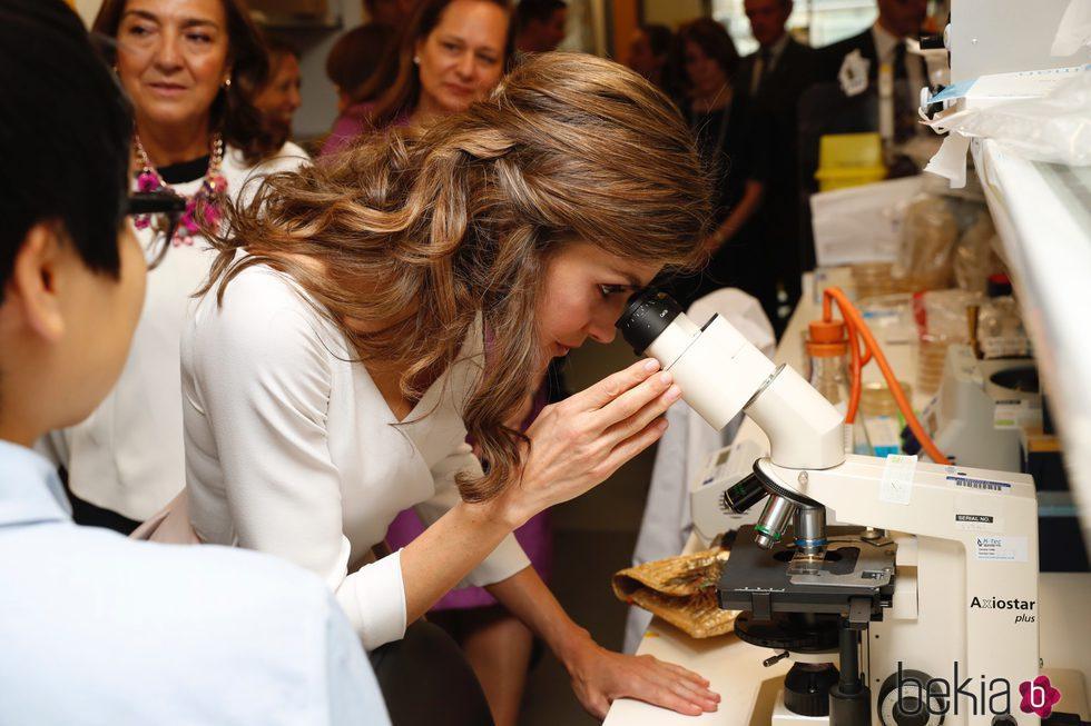 La Reina Letizia mirando por un microscopio durante su visita oficial a un laboratorio en Reino Unido