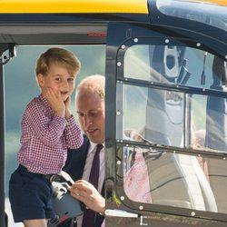 El Príncipe Jorge explorando un helicóptero en Hamburgo bajo la atenta mirada de Guillermo de Inglaterra