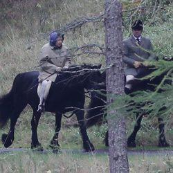 La Reina Isabel montando a caballo con su monitor