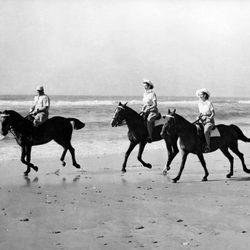 La Reina Isabel y la Princesa Margarita montando a caballo en la playa de jóvenes