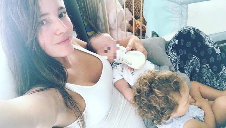 Malena Costa con su hija Matilda mientras da el biberón a su hijo Mario