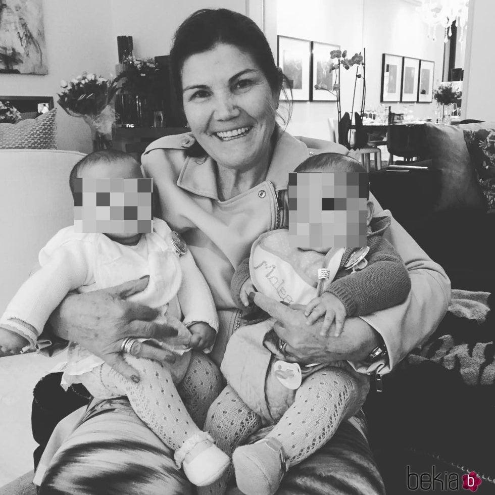 Dolores Aveiro sujetando en brazos a sus nietos mellizos Mateo y Eva