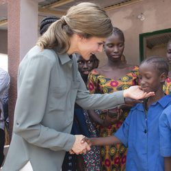 La Reina Letizia con un niño en la granja Naatangué de Senegal