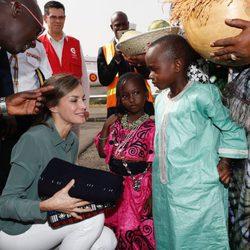 La Reina Letizia recibe unos regalos de unos niños en su despedida de Senegal