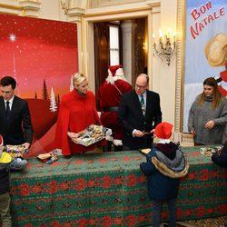 Alberto y Charlene de Mónaco reparten regalos a los niños junto a Louis Ducruet y Camille Gottlieb