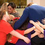 El Príncipe Harry y Meghan Markle, abrazados por unas niñas galesas