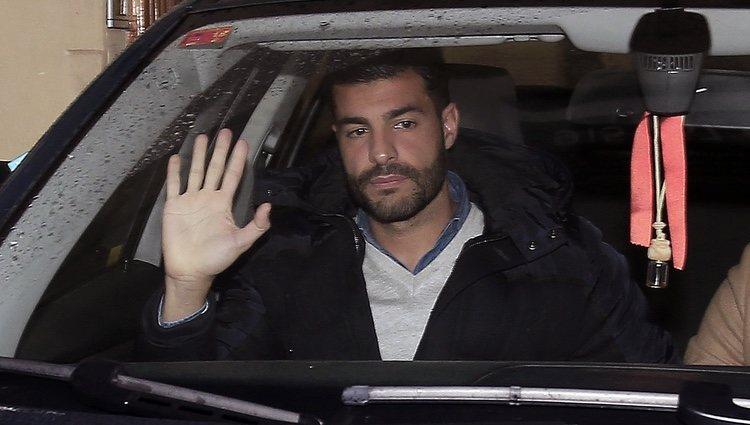 Miguel Torres montado en un coche mientras saluda a la prensa