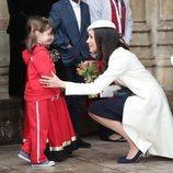 Meghan Markle se agacha para hablar con una niña en el Día de la Commonwealth 2018