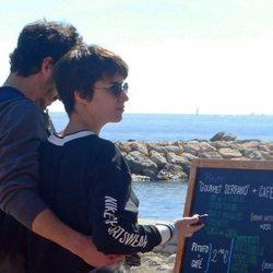 Chino Darín y Úrsula Corberó mirnado un menú en la playa de Málaga