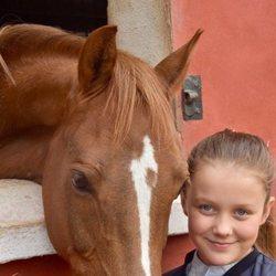 Isabel de Dinamarca sonriente junto a un caballo en su onceavo cumpleaños
