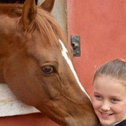 Isabel de Dinamarca feliz junto a un caballo en su onceavo cumpleaños