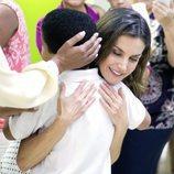 Doña Letizia abraza efusivamente a un niño durante su viaje de cooperación a República Dominicana