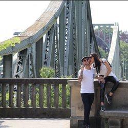Pilar Rubio dando un beso a Sergio Ramos con un puente de fondo