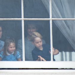 El Príncipe Jorge y la Princesa Carlota con su niñera mirando por una ventana de Buckingham Palace