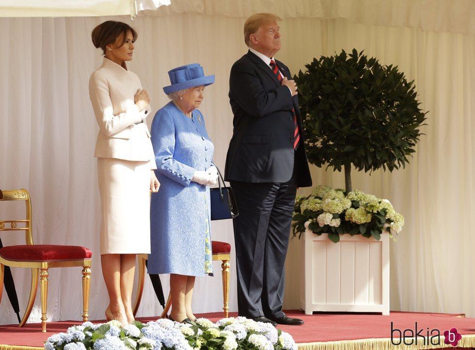 Los Trump con la mano en el corazón junto a la Reina Isabel II