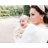 La Duquesa de Cambridge muy sonriente junto a un divertido  Príncipe Luis en el día de su bautizo