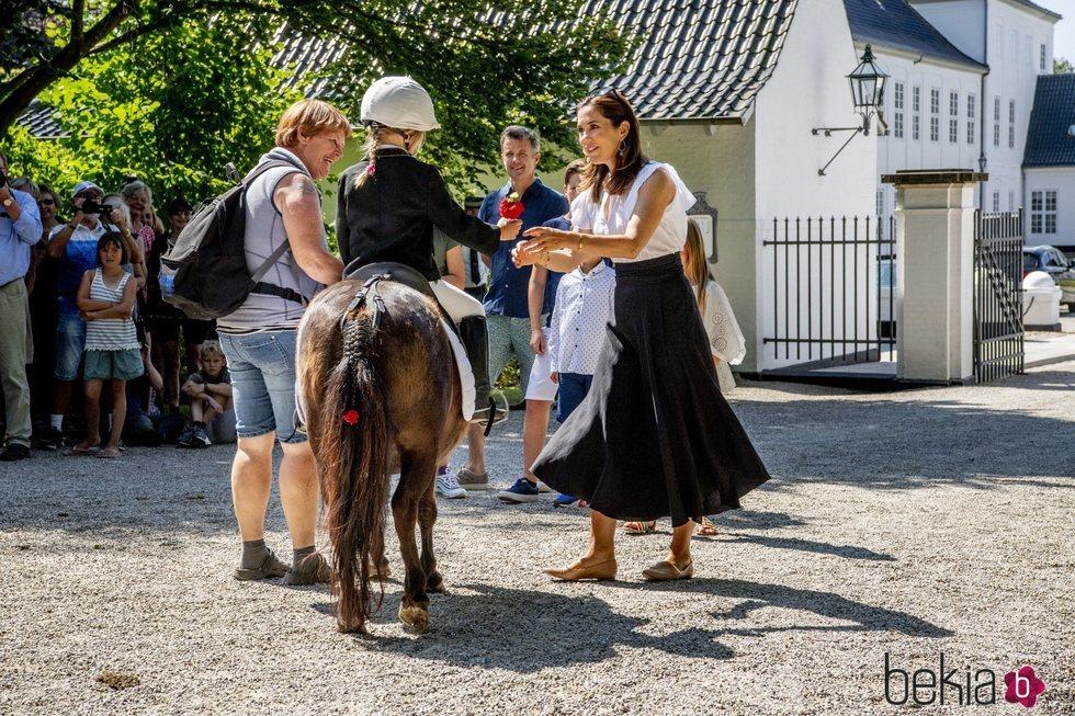 La Princesa Mary de Dinamarca junto a una de las jinetes del tradicional desfile de verano en el Palacio de Grasten