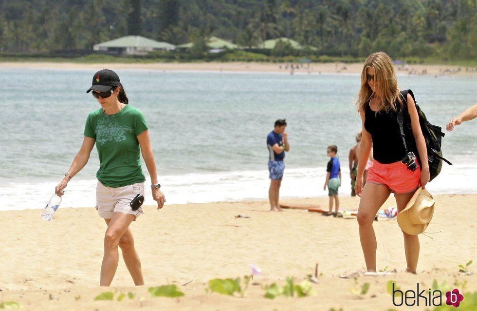 Courteney Cox y Jennifer Aniston paseando por una playa de Hawái