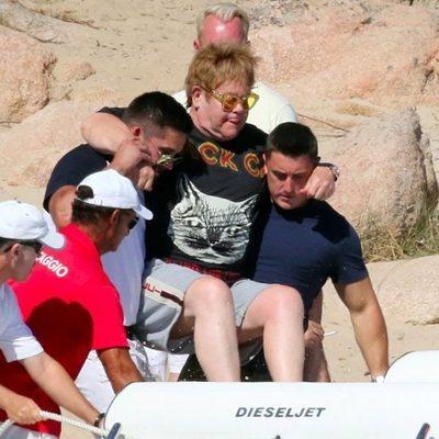Elton John siendo ayudado para subirse a una pequeña embarcación en Cerdeña