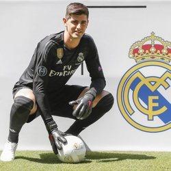 Thibaut Courtois posando con la equipación del Real Madrid
