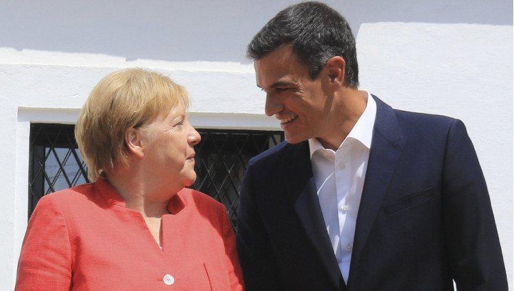 Pedro Sánchez y Angela Merkel se miran sonrientes durante la visita de la canciller al Palacio de los Guzmanes