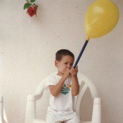 Cepeda de niño inflando un globo