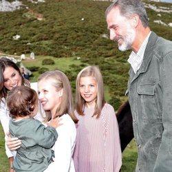 La Princesa Leonor sostiene a una niña en brazos en presencia de los Reyes Felipe y Letizia y la Infanta Sofía en Covadonga