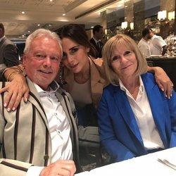 Victoria Beckham y sus padres durante el desfile de la London Fashion Week