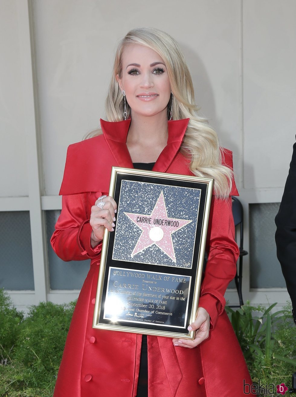 Carrie Underwood posando con su estrella en el Paseo de la Fama de Hollywood